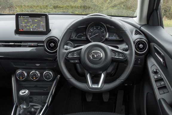 The interior of a Mazda 2 with steeringwheel and dashboard in shot