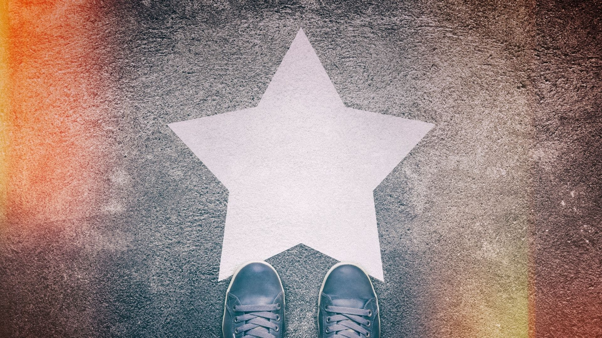 A pair of shoes standing near a star painted on the ground