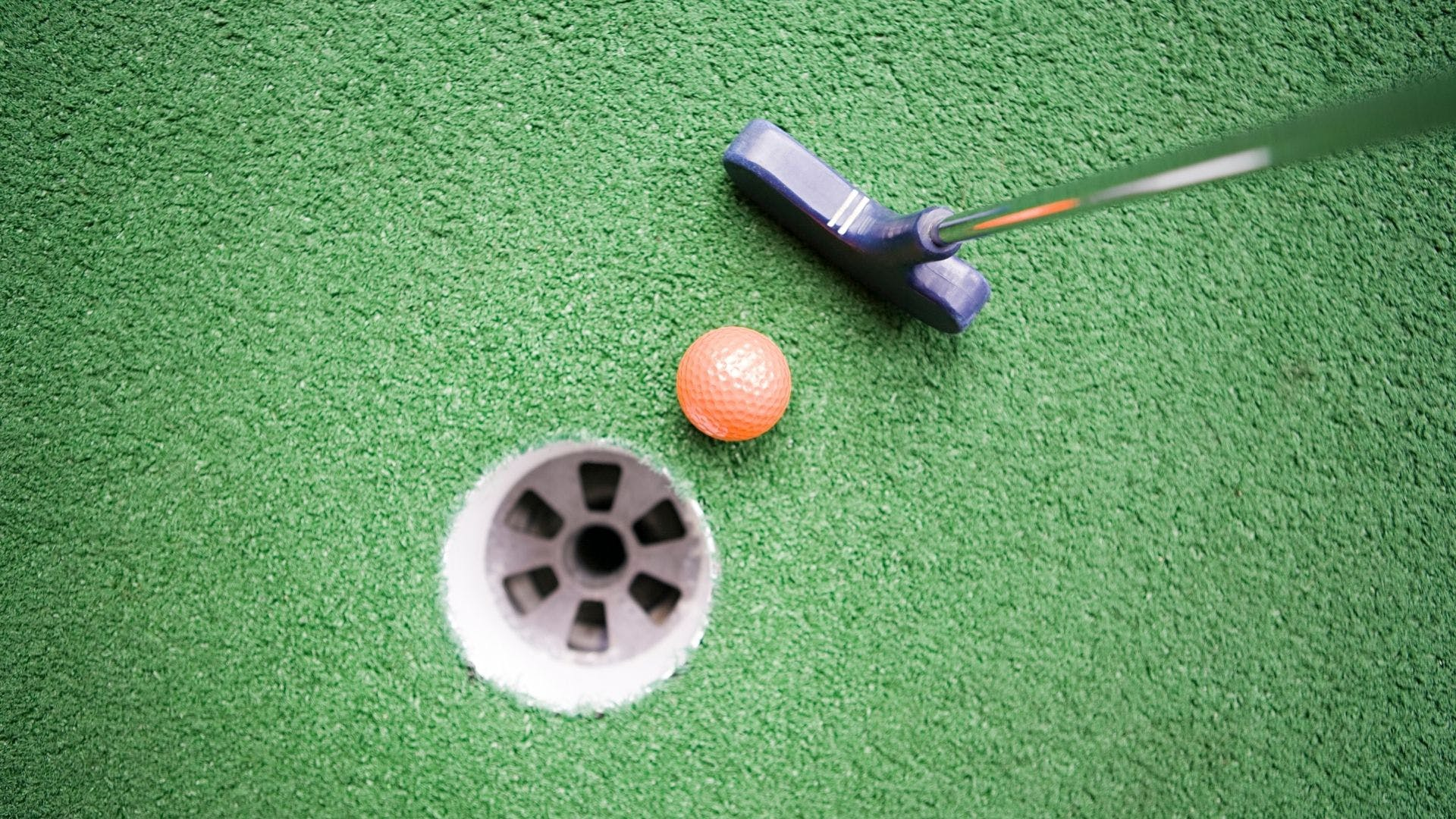 A birds eye view of a mini golf ball going into the hole