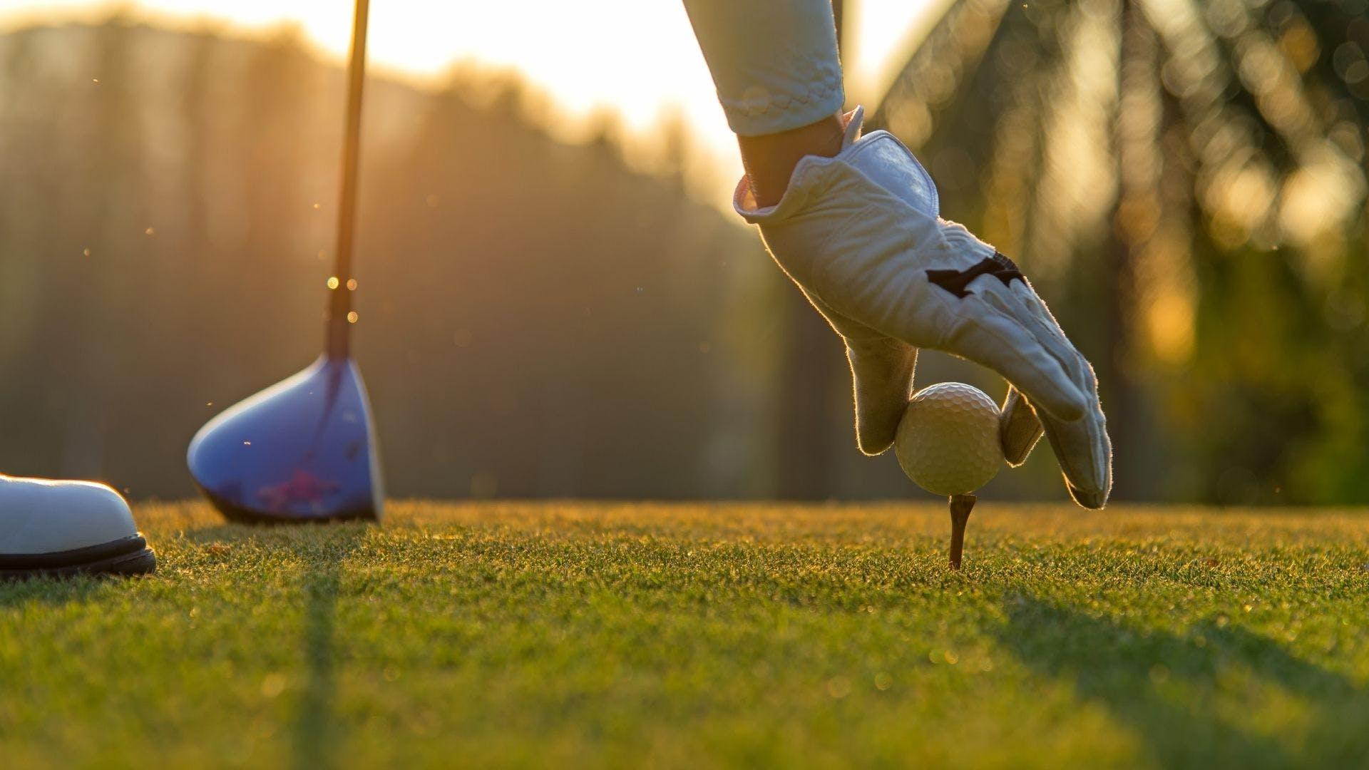 A hand resting a golf ball on a tee