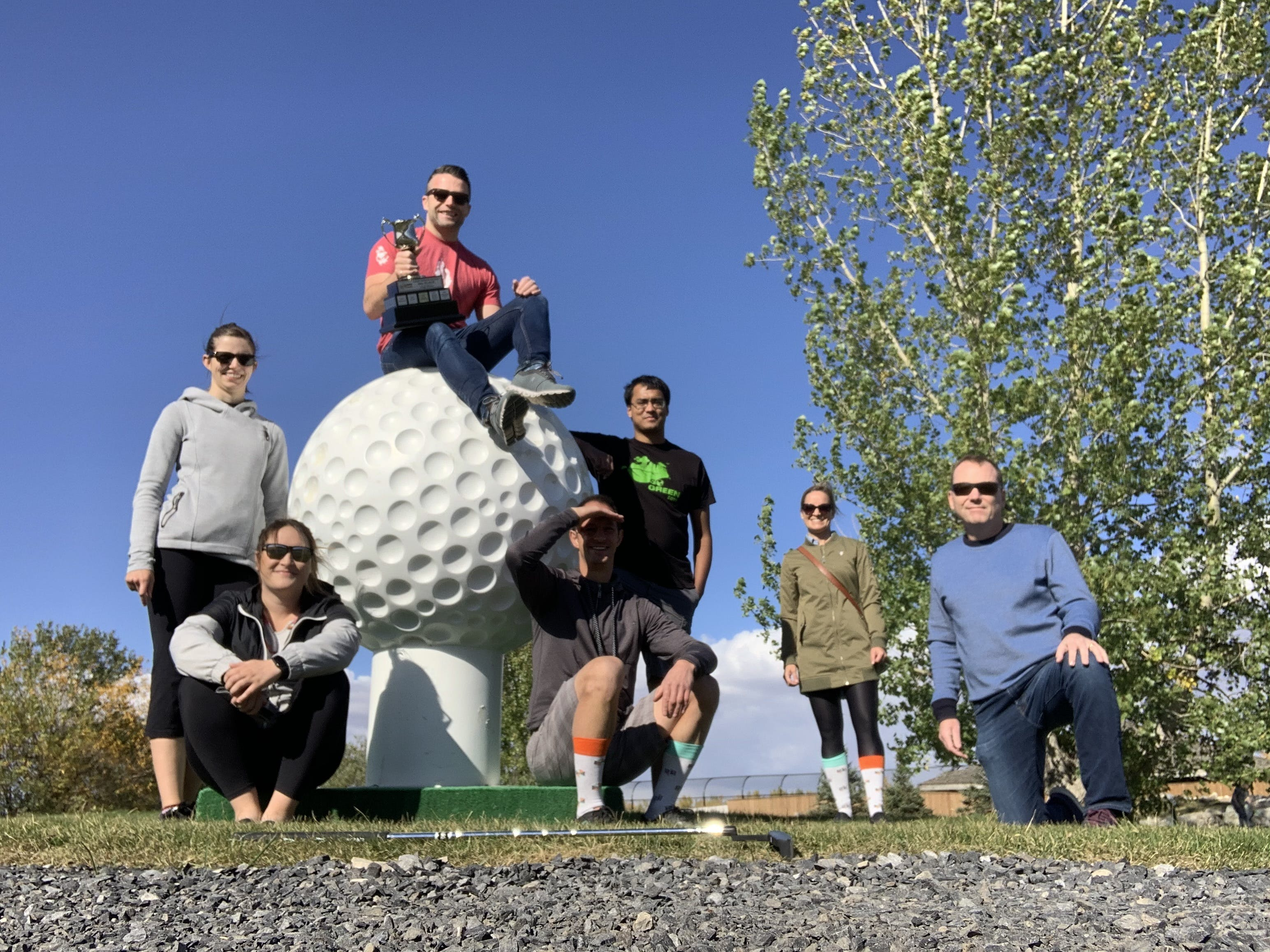Group of people posing around giant golf ball