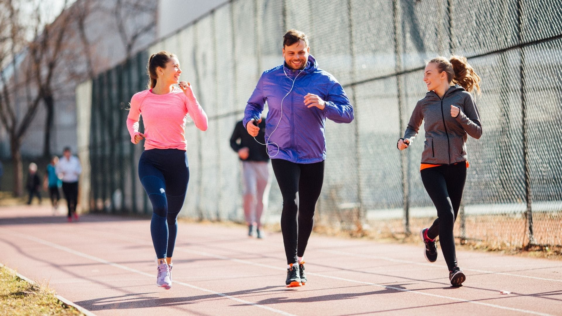 Three people running and smiling