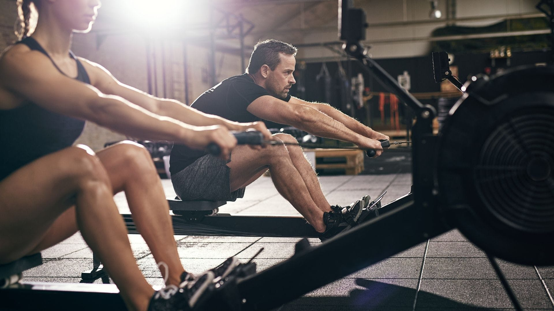A man and a woman on rowing machines