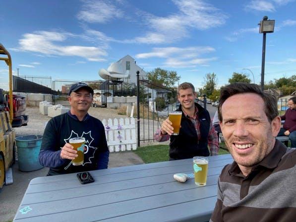 Three men holding beer