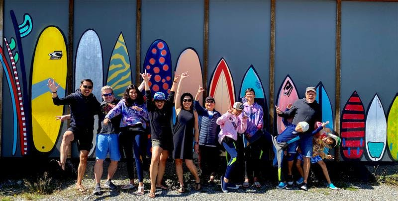 People standing in front of painting of surfboards on wall