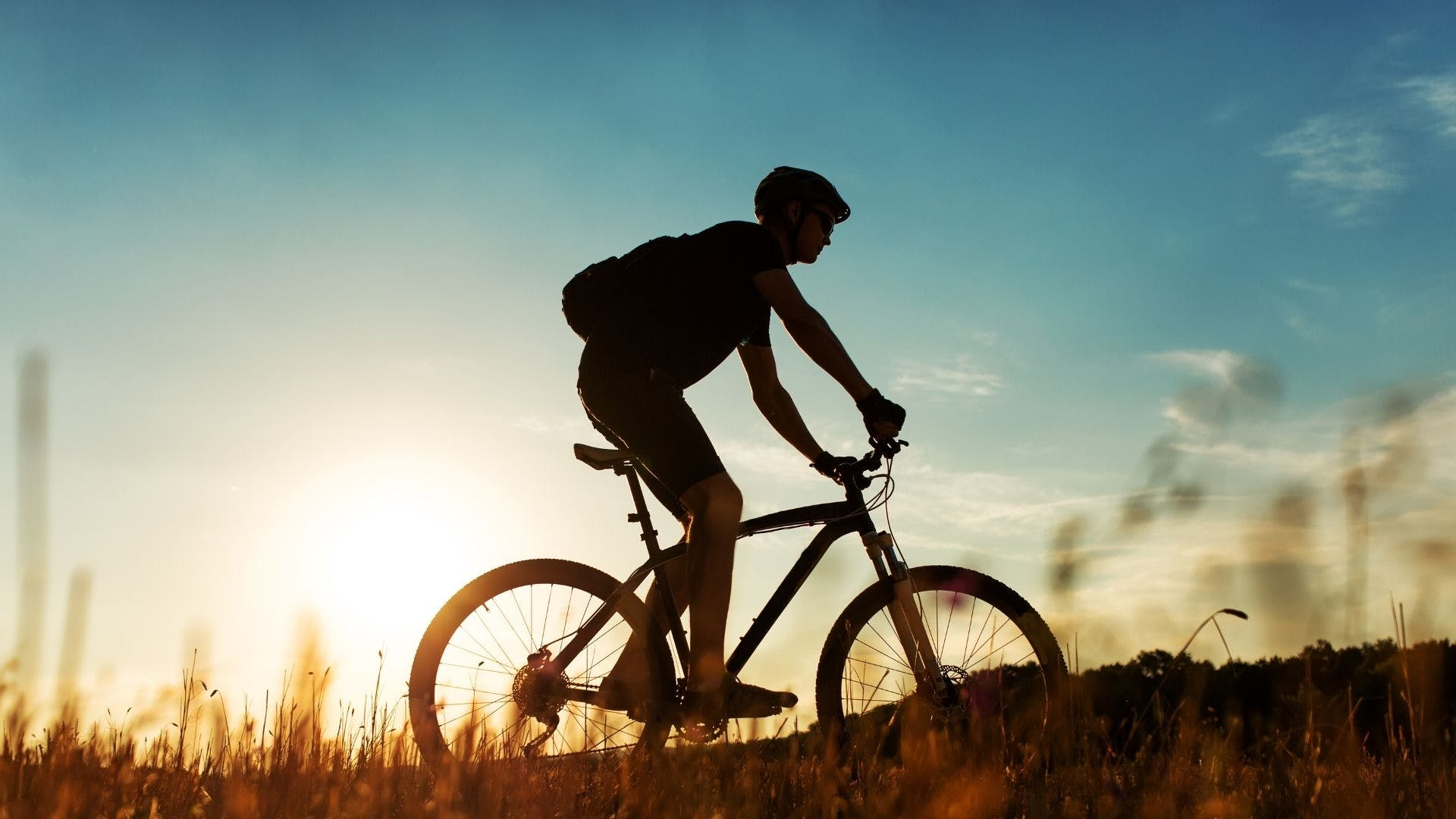 A person cycling in front of a sunset