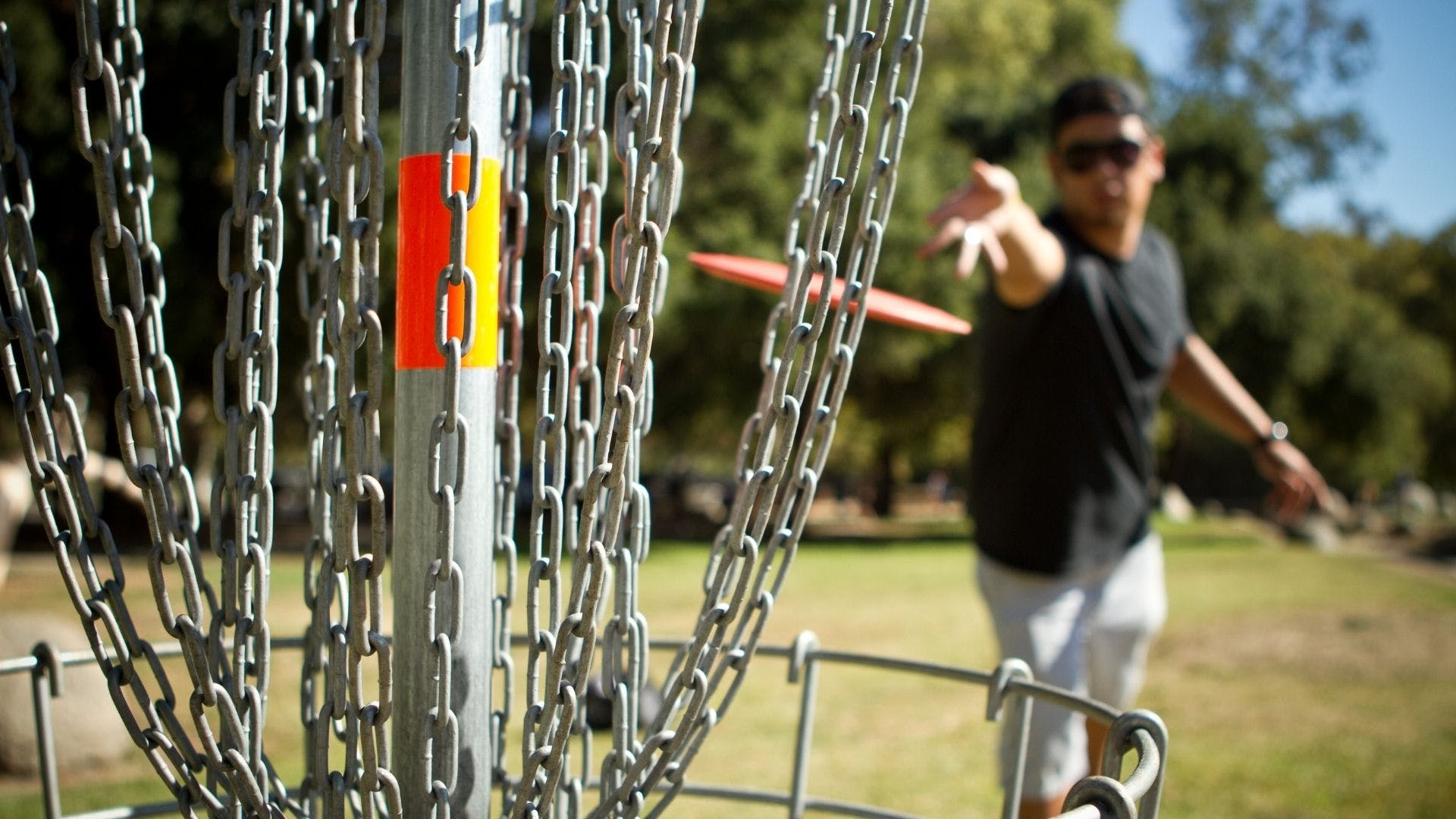 Player in background throwing a disc golf into the basket in the foreground