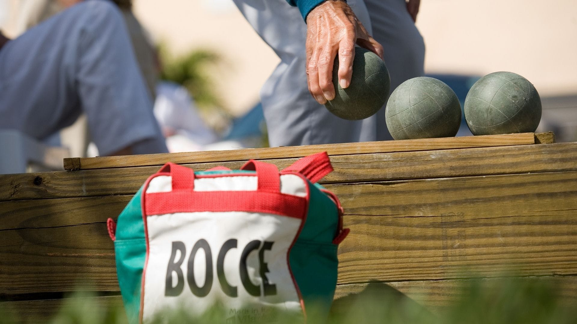 Player picking up bocce ball with a bocce bag in foreground