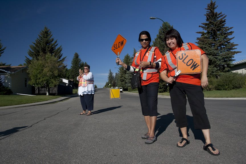 Volunteers holding slow signs at running event