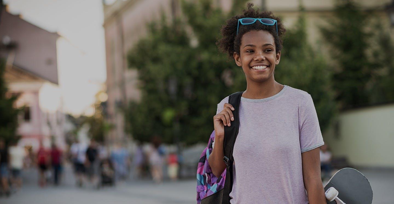Girl with sun glasses holding skateboard