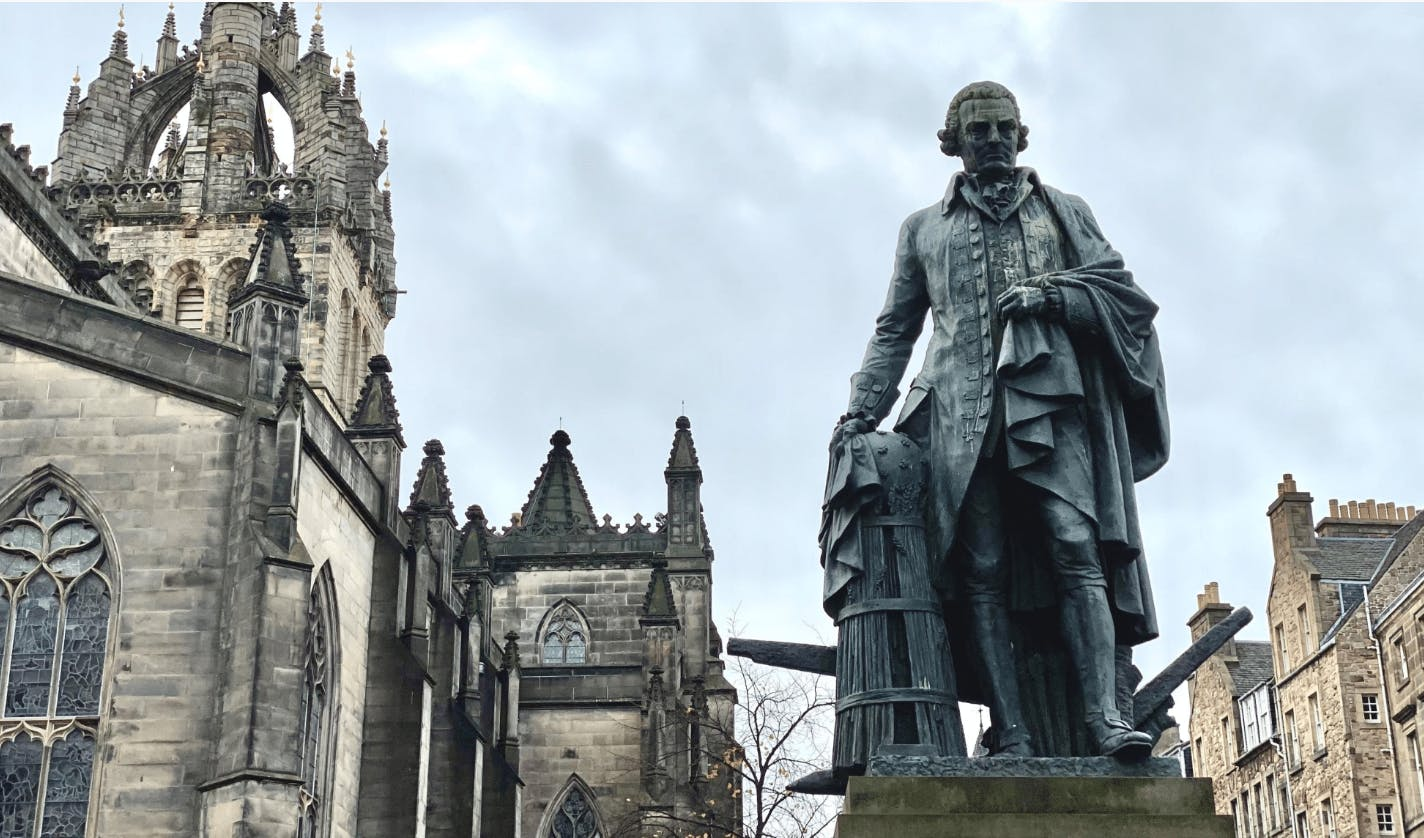 Photo by Matt May of Adam Smith statue on Edinburgh's Royal Mile, standing beside something that resembles a dalek