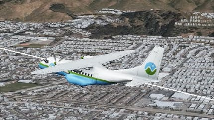 3D model of a Cesium branded airplane on a flight path over 3D buildings and terrain