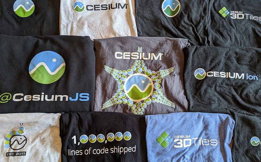 Eleven t-shirts in different colors folded so you can see the Cesium logo and design on each of them.