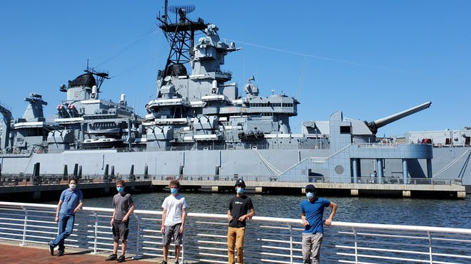 Five members of the Cesium team standing in front of the U.S. Battleship New Jersey outside of Philadelphia