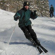 A man in a green coat skiis.