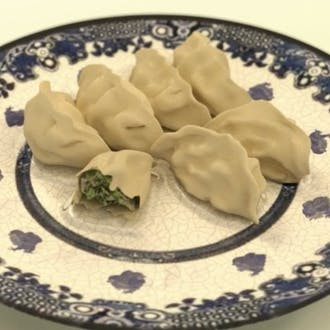 Seven dumplings on an ornate blue and white plate.