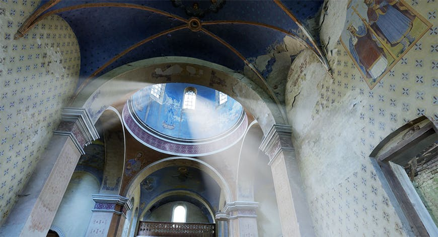Interior view of the historic Oleszyce Church in Poland, looking up into a domed ceiling painted with blue artwork