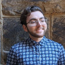 Alex Gallegos smiling and wearing a patterned blue shirt