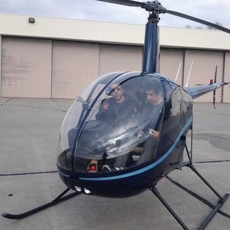 Sam Suhag in the cockpit of a grounded helicopter.
