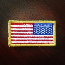 An American Flag patch with a gold border