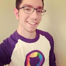 A man with glasses wears a GitHub shirt and smiles.
