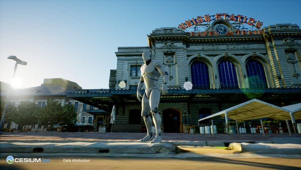 A ground-level view of Union Station in Denver, seen in Unreal Engine. A UE male mannequin is standing on the sidewalk.