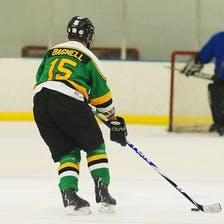 A man skates on ice wearing in a green and gold hockey uniform.