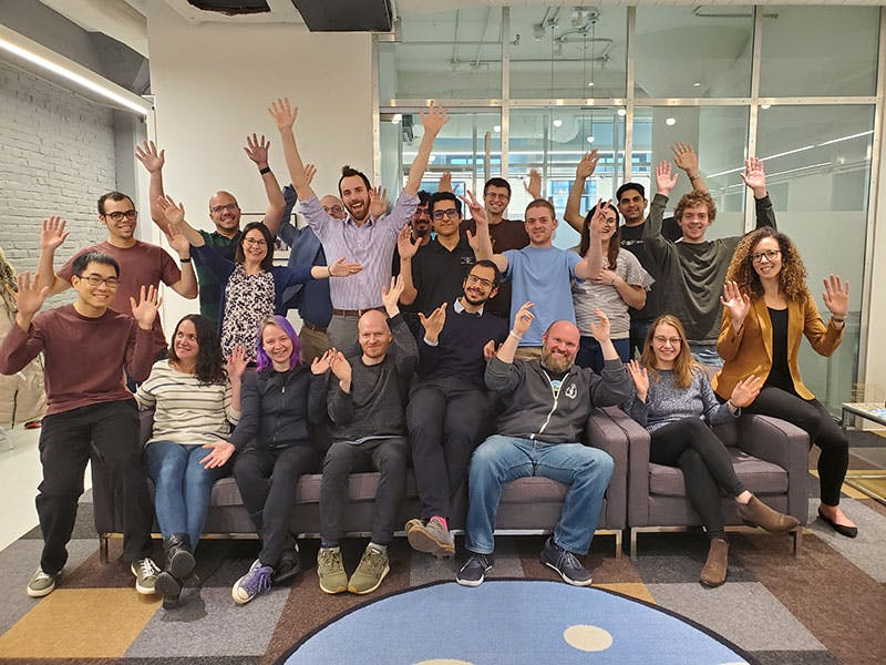 Members of the Cesium Team together in a bright open space, waving their arms in celebration.