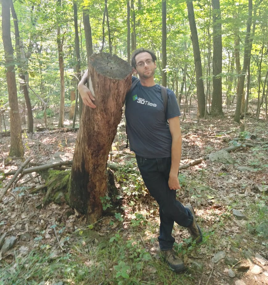 Daniel Krupka, wearing a 3D Tiles shirt, stands in the woods with his arm around a tall tree stump.
