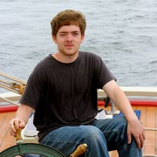 Sean Lilley squinting as he steers a boat.