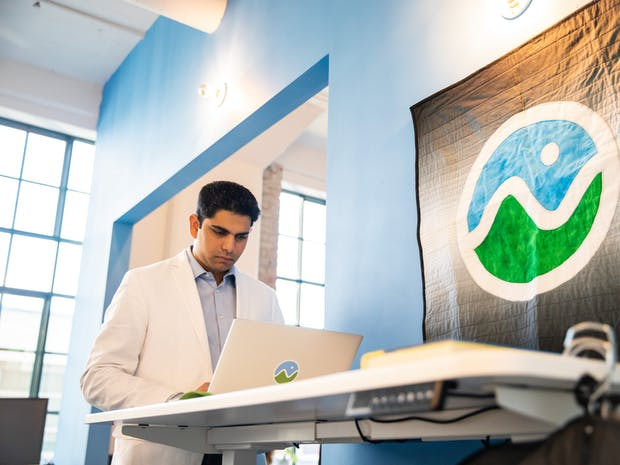A man in a white blazer uses a laptop at a standing desk next to a Cesium quilt.