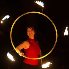 Hannah Pinkos spins a flaming hoop.