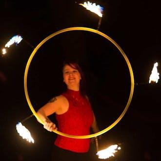 Hannah Pinkos spins a flaming hoop.