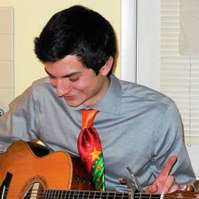 A man in a red tie plays an acoustic guitar.