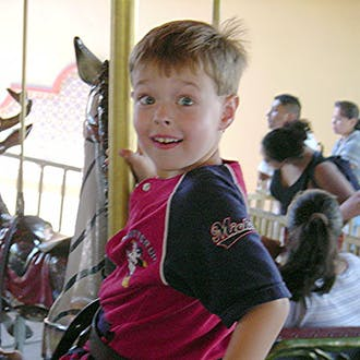 Josh Rouzer on a carousel as a child.