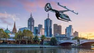 concept image of an aerial Uber vehicle flying over a river at the edge of a city skyline at sunset