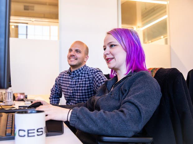 A woman with purple hair works at a computer, joined by a man in a checkered shirt. A cesium coffee mug is in the foreground.