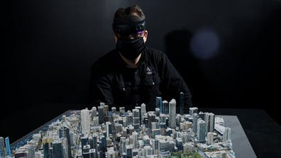 Man wearing a mask and VR headset standing over a digital 3D model of a city