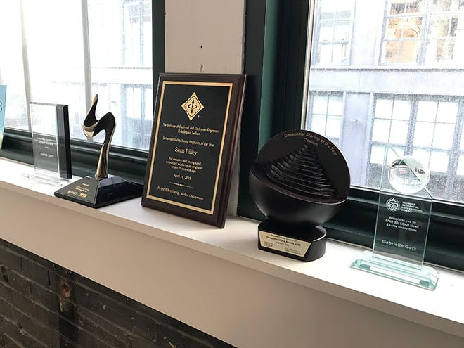 The Geospatial Startup of the Year and 2020 Technology Startup Enterprise Award trophies on a windowsill in downtown Philadelphia.