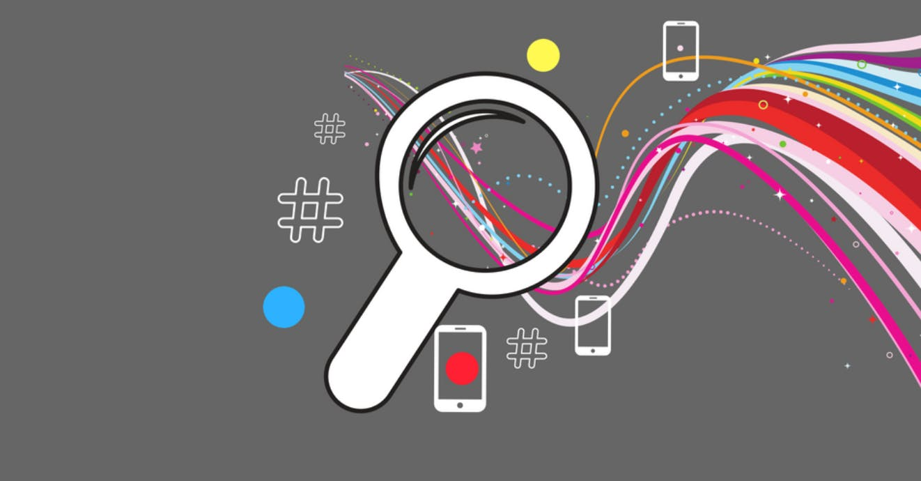 An illustration of a magnifying glass with colourful lines flowing through and out of the frame.