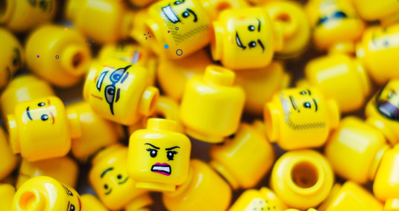 Pile of yellow LEGO heads with varying expressions.