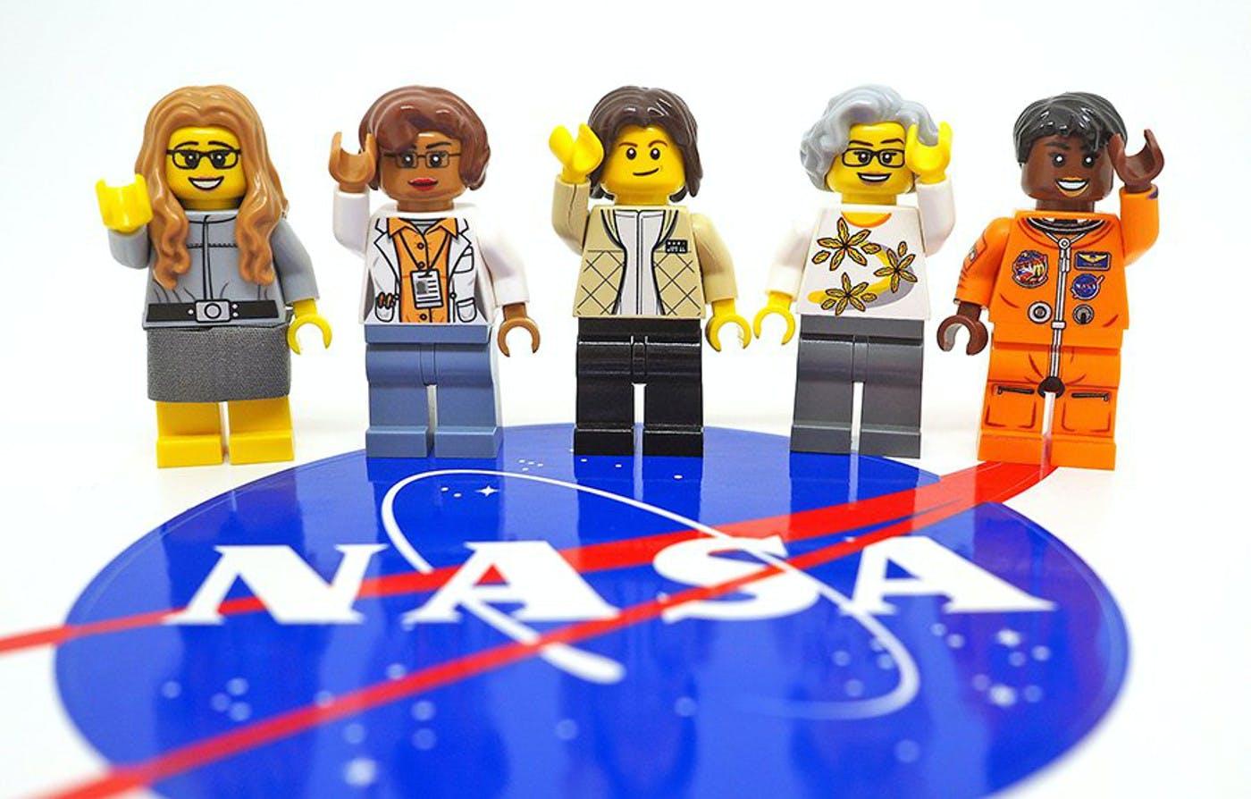 Five LEGO figures standing on the NASA logo.