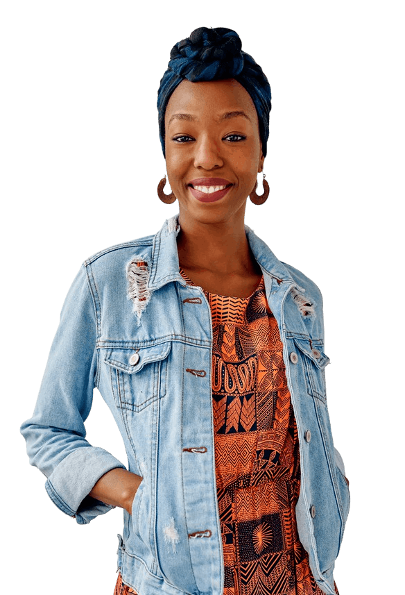 A cheerful woman smiling with her hands placed in her jean jacket pockets