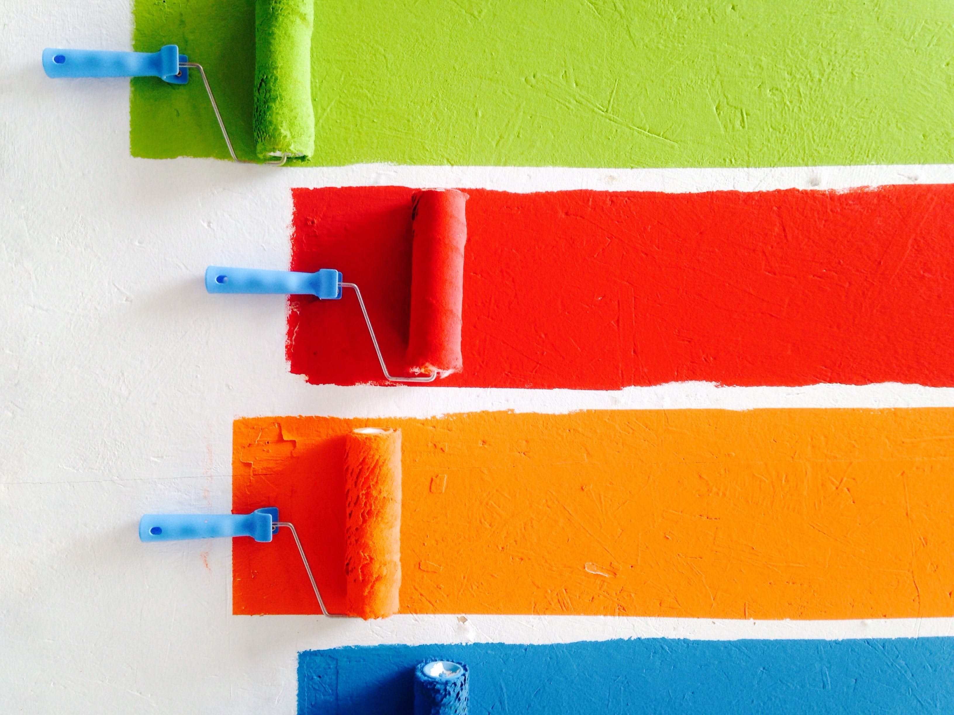Four paint rollers painting different colours side by side.