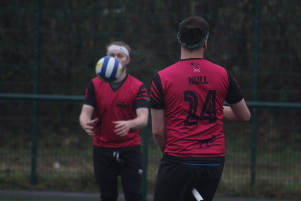 Two players pass a quaffle