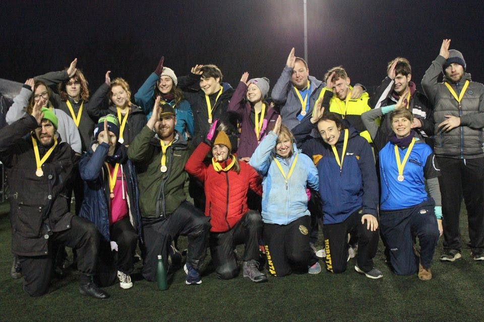 """Megladons pose for a photo with their bronze medals, all making a """"fin"""" sign on their heads"""