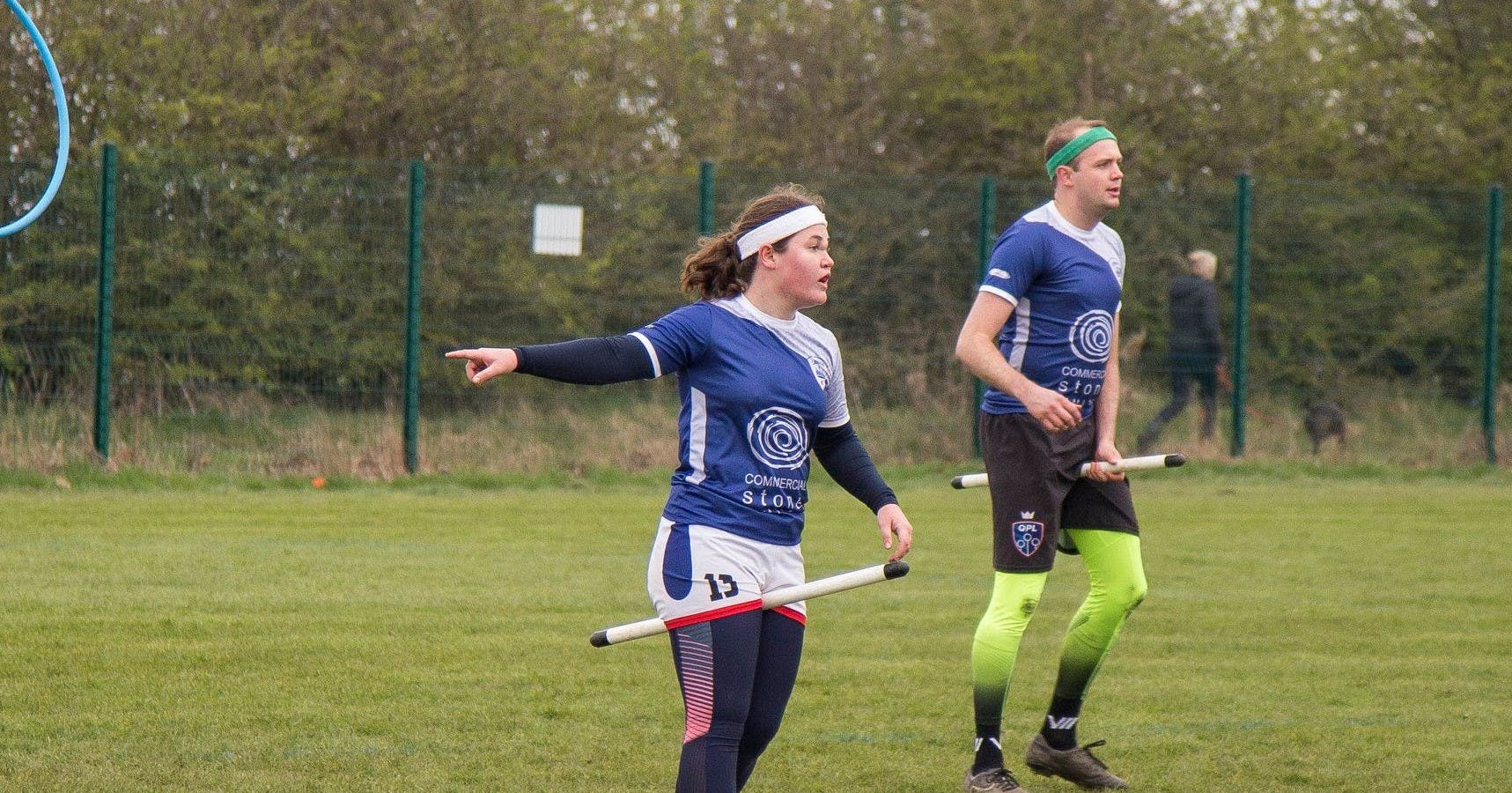 Bex Lowe points to something off-pitch while chasing during a match