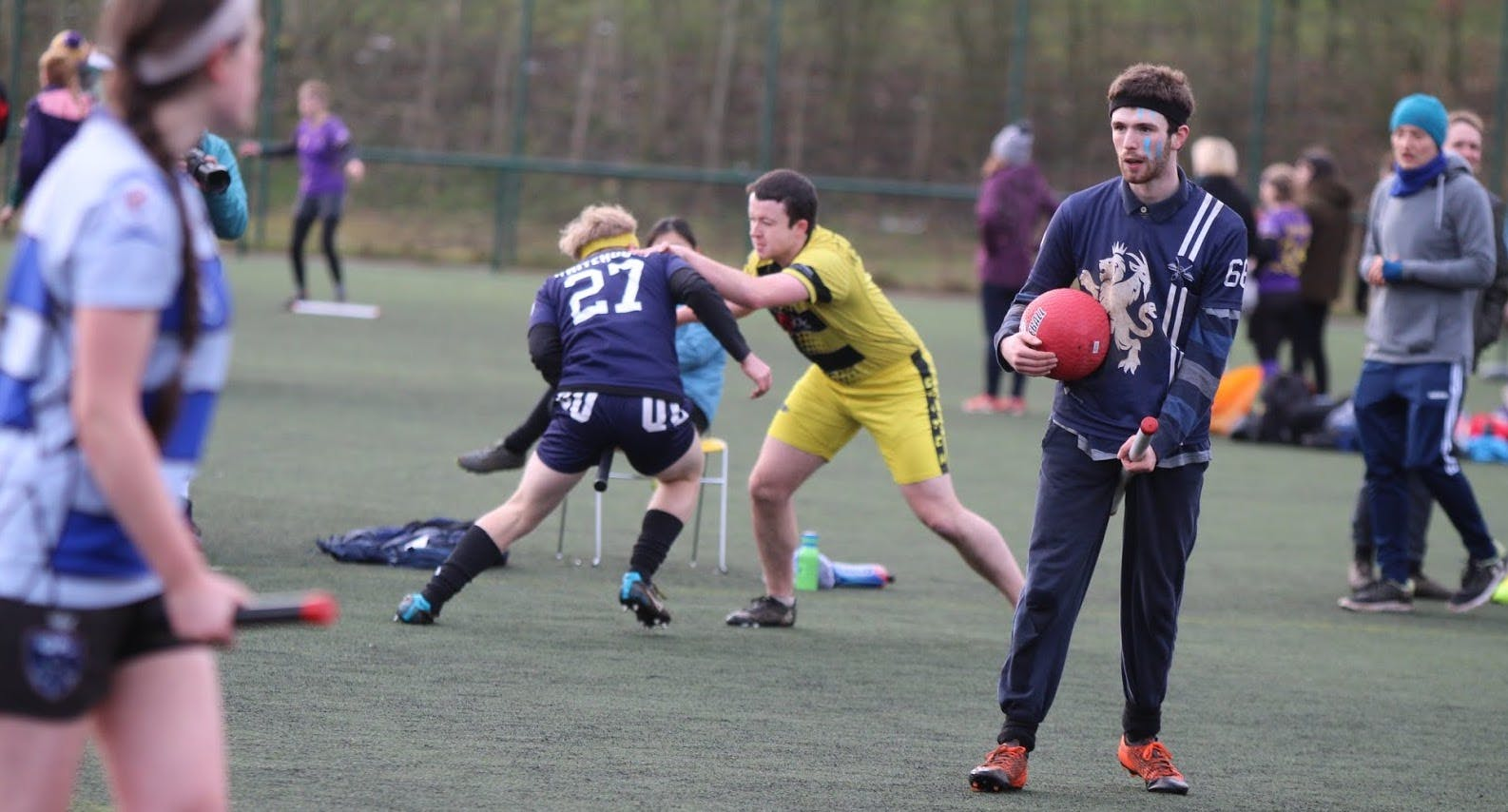 A player and a snitch wrestle while a beater guards them