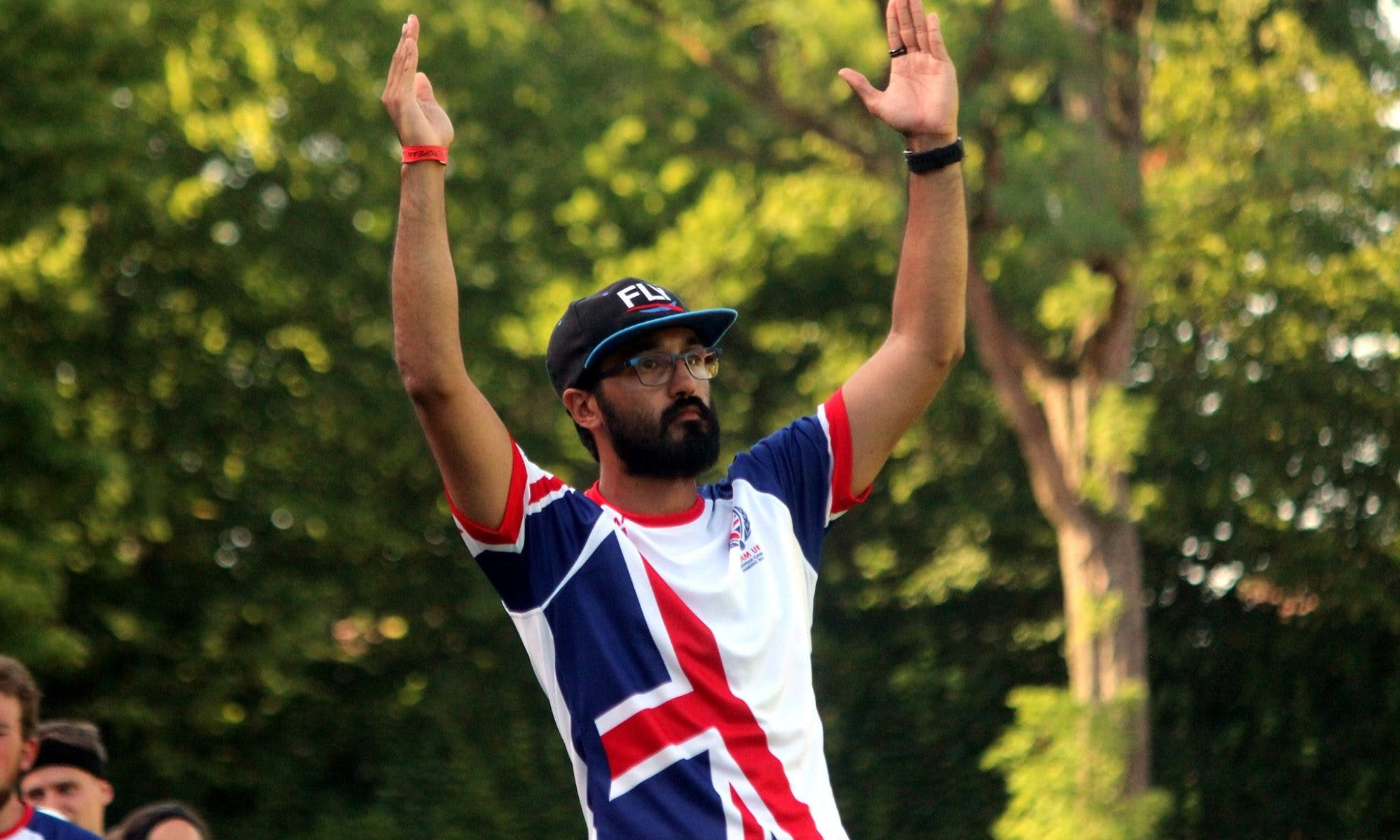 James Thanangadan stands wearing a Team UK Kit with his arms raised to indicate a goal
