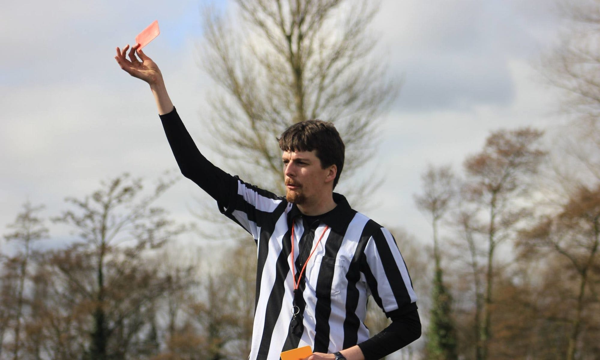Eamonn Harrison holds a red card while refereeing a Quidditch match